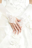 Bride's hands with manicure in white  lace gloves. Closeup Royalty Free Stock Photography