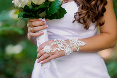 Bride's hands with manicure in white lace gloves Royalty Free Stock Photo
