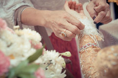 The brides hands are tied with thread Stock Photos