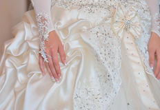 Bride's hands on wedding dress Royalty Free Stock Photos