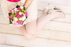 Bride's legs and flowers on wooden floor Stock Photos