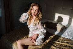 Bride`s morning. Fine art wedding. Portrait of a young bride in white lace boudoir with wavy blonde hair and a bouquet Royalty Free Stock Photography