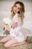 Bride`s morning. Fine art wedding. Portrait of a young bride in white lace boudoir with wavy blonde hair and a bouquet Royalty Free Stock Photos