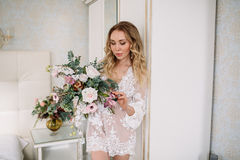 Bride`s morning. Fine art wedding. Portrait of a young bride in white lace boudoir with wavy blonde hair and a bouquet Royalty Free Stock Images