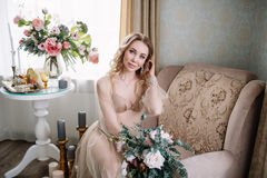 Bride`s morning. Fine art wedding. Portrait of a young bride in white lace boudoir with wavy blonde hair and a bouquet Royalty Free Stock Image