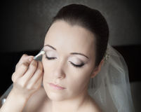 Bride's Preparation. Beautiful bride having her make-up done by a professional artist Royalty Free Stock Images