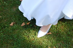 Bride's Shoe. A bride walking in a park in her wedding dress and white shoes Royalty Free Stock Photos