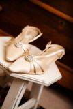 The Bride's Shoes. Fancy pointed wedding heels on a stool with church pews in the background stock images