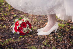 Bride's shoes and bouquet on the grass Stock Photography