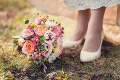 Bride's shoes and bouquet on the grass Stock Image