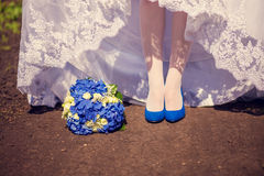 Bride's shoes and bouquet on the grass Stock Photos