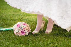 Bride's shoes and bouquet on the grass Stock Photo