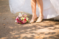 Bride's shoes and bouquet on the grass Royalty Free Stock Image