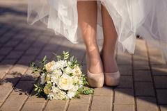 Bride's shoes and bouquet on the grass Stock Images