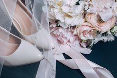 Bride`s shoes and a bouquet of peonies close-up. Gentle color and veil royalty free stock image