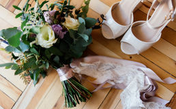 Bride`s shoes and a bridal bouquet. On the parquet Stock Image