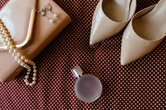 Bride`s shoes, garter, perfume, necklace and clutch. Bride`s shoes, perfume, necklace and clutch are on burgundy cloth surface Stock Image