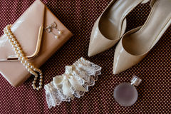 Bride`s shoes, garter, perfume, necklace and clutch. Bride`s shoes, garter, perfume, necklace, earrings and clutch are on burgundy cloth surface Stock Image