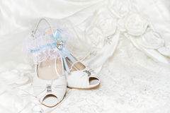 Bride's shoes, garter, wedding dress. Bride's shoes garter, with blue ribbon, wedding dress. Closeup of wedding accessories Royalty Free Stock Image