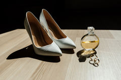 Bride`s shoes, perfume and wedding rings. Are on the table Royalty Free Stock Photography