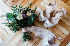 Bride`s shoes and wedding bouquet. Bride`s shoes and a bridal bouquet on the parquet Stock Image