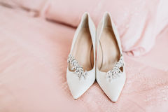Bride`s shoes for the wedding day on bed sheet Stock Photo