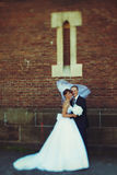 Bride`s veil covers groom`s head while wind blows along them Royalty Free Stock Photography