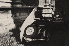 Bride's veil hangs down while she sits with groom on a retro car stock photography