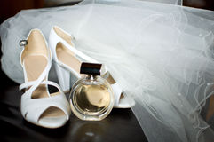 Bride's veil with shoes and parfume on leather armchair Royalty Free Stock Photos