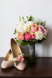 Bride`s wedding accessories: wedding shoes and bouquet or boutonniere Stock Image