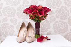 Bride`s wedding accessories: wedding shoes and bouquet or boutonniere Royalty Free Stock Image