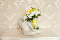 Bride`s wedding accessories: wedding shoes and bouquet or boutonniere Royalty Free Stock Photo