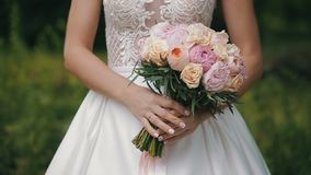 Bride is holding a wedding bouquet of roses and peonies. Bridal bouquet on wedding day. Bouquet of different flowers stock footage