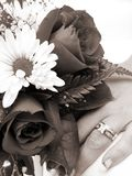 Bride's wedding ring hand and bouquet closeup sepia Stock Images