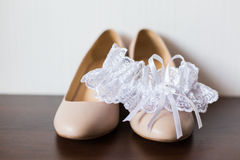 Bride`s wedding shoes and garter. Stock Images