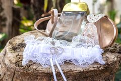 Bride`s white, lace garter, shiny shoe and golden perfume staged outside. On raw wood royalty free stock photo