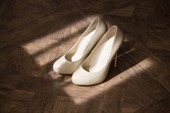 Bride's white shoes. White shoes of the bride in the rays of light on the floor Royalty Free Stock Photos