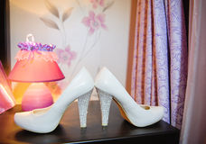 Bride's white shoes on the table Royalty Free Stock Photos
