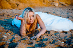 Bride on sand at sunset. Trash the wedding dress series. Bride lying on sand and looking at camera, she looks tired royalty free stock photo