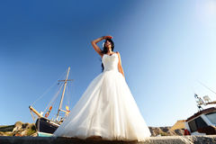 Bride on a Santorini harbor. A wide shot of a bride looking far away, from a harbor in Santorini - Greece Royalty Free Stock Images