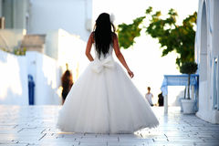 Bride in Santorini, view from behind. A shot with a bride in Oia, Santorini - taken from behind the subject with the back side of the dress visible Royalty Free Stock Photo