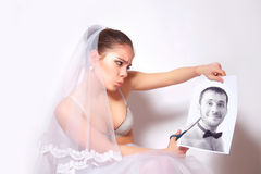 Bride scissor a photo which shows the groom Royalty Free Stock Photography