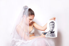 Bride scissor a photo which shows the groom Stock Images