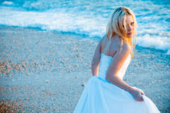 Bride on sea coast. Looks tired, she is entering water, holding her wedding dress and looking back at camera royalty free stock photos