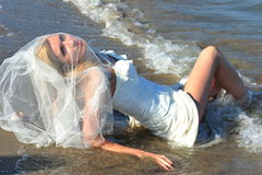 Bride of the sea - trash the wedding dress stock photo