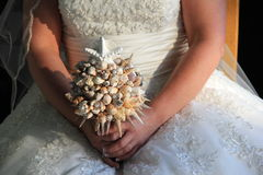 Bride seated in chair, holding bouquet of shells Stock Image
