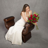 Bride seated with roses, studio shot Royalty Free Stock Photos