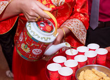 The bride serving the tea for the elders. The chinese bride serving the tea for the elders, text on the teapot saying the same mind Royalty Free Stock Image