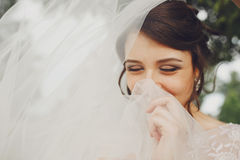Bride shines standing with closed eyes and hiding her smile behind a veil stock image