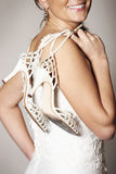 Bride and shoes. A picture of a happy bride holding her wedding shoes and smiling Royalty Free Stock Images